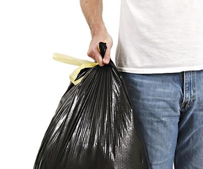 A man carrying a trash bag